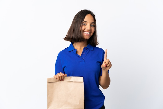 Молодая латинская женщина держа сумку посещения магазина бакалеи изолированная на белизне показывая и поднимая палец