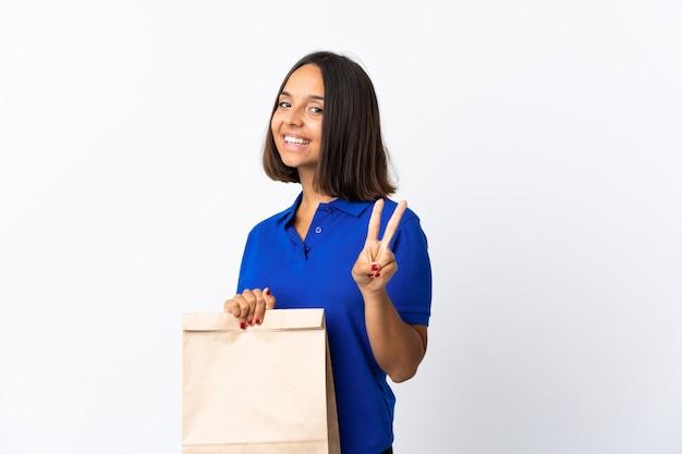 Молодая латинская женщина держа сумку посещения магазина бакалеи изолированная на белизне усмехаясь и показывая знак победы