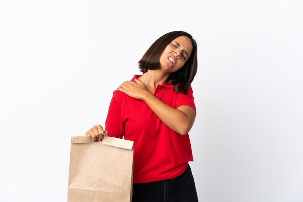 Молодая латинская женщина, держащая сумку для покупок, изолированная на белом, страдает от боли в плече за то, что приложила усилие