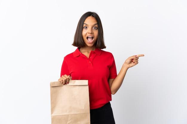 Молодая женщина латинской держит продуктовый мешок, изолированных на белом удивлен и указывая пальцем в сторону
