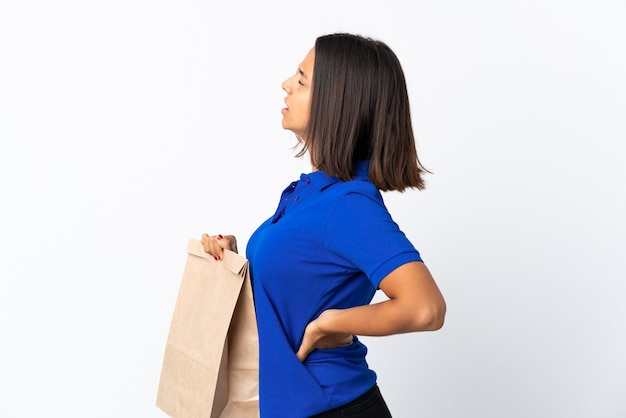 食料品の買い物袋を持っている若いラテン女性