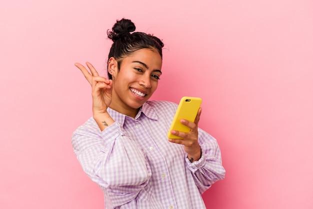 ピンクの背景に分離された携帯電話を持つ若いラテン女性は、指で平和のシンボルを示す、うれしくて屈託のない。
