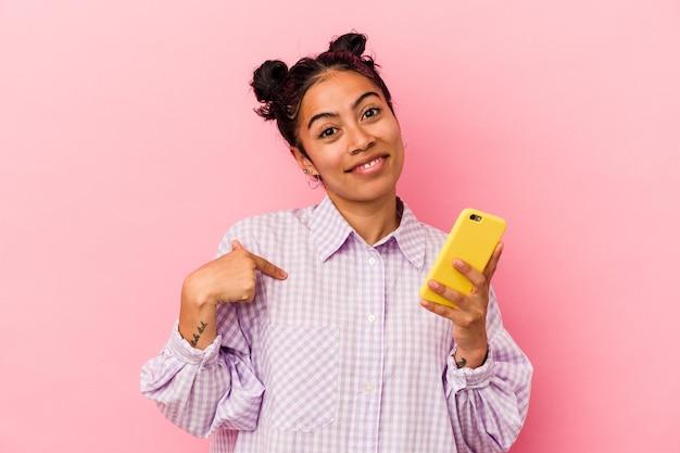 자랑스럽고 자신감, 셔츠 복사 공간을 손으로 가리키는 분홍색 배경 사람에 고립 된 휴대 전화를 들고 젊은 라틴 여자