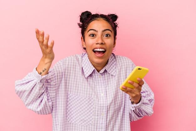 ピンクの背景に携帯電話を持った若いラテン女性が、うれしい驚きを受け取り、興奮して手を上げている。