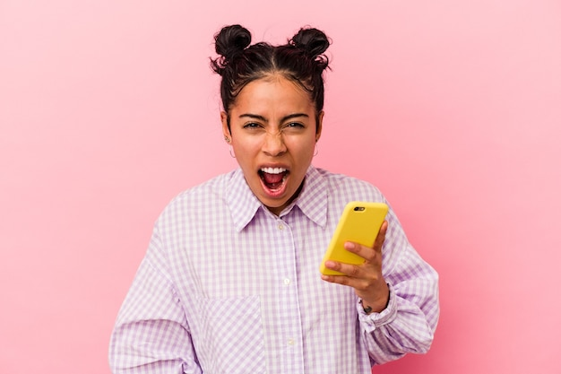 Молодая латинская женщина, держащая мобильный телефон, изолирована на розовом фоне, кричала очень сердито и агрессивно.