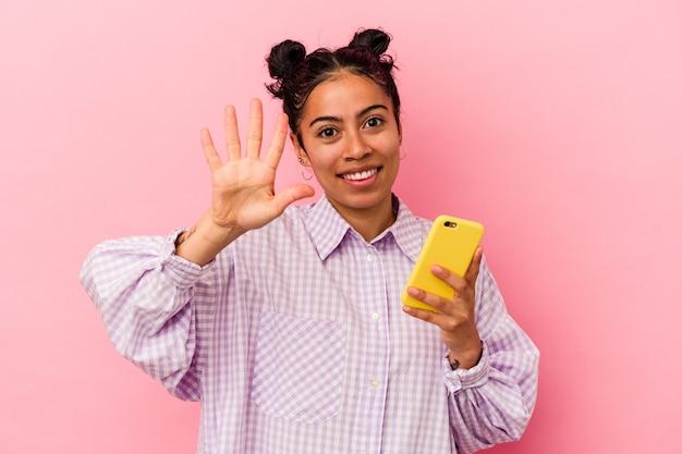 ピンクの背景に携帯電話を持つ若いラテン女性が、指で5番を示す陽気な笑顔を浮かべています。