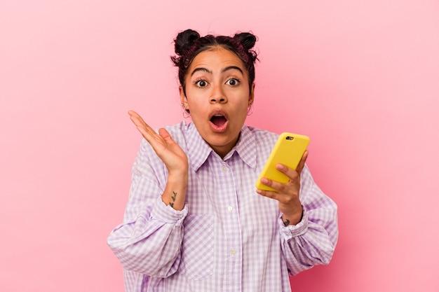 분홍색 배경에 고립 된 휴대 전화를 들고 젊은 라틴 여자 놀라게 하 고 충격.