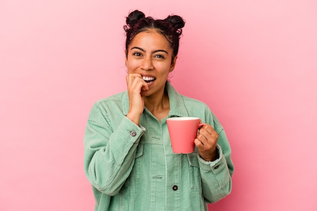 Молодая латинская женщина держит кружку, изолированную на розовом фоне, кусая ногти, нервничает и очень тревожится.