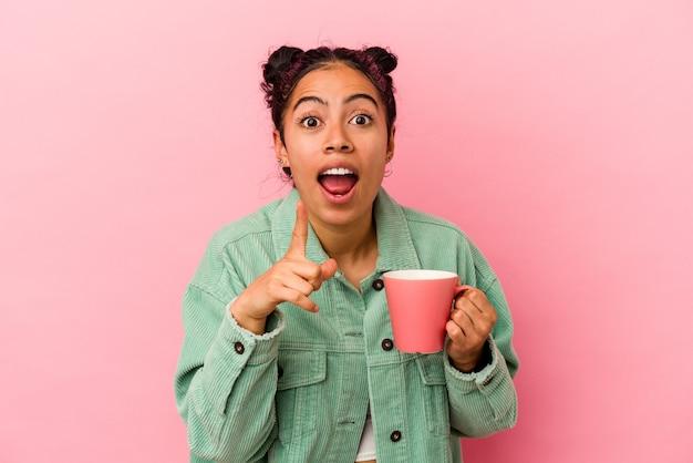 アイデア、インスピレーションの概念を持つピンクの背景に分離されたマグカップを保持している若いラテン女性。