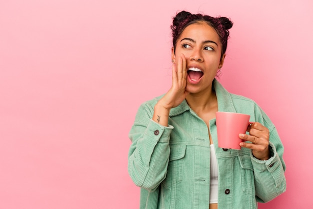 Молодая латинская женщина, держащая кружку на розовом фоне, говорит секретные горячие новости о торможении и смотрит в сторону