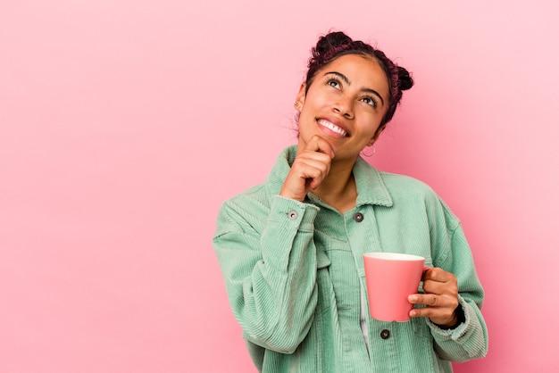 Молодая латинская женщина, держащая кружку на розовом фоне, смотрит в сторону с сомнительным и скептическим выражением лица.
