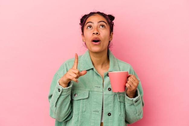 Молодая латинская женщина держит кружку, изолированную на розовом фоне, указывая вверх с открытым ртом.