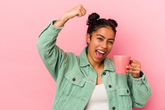 Молодая латинская женщина держит кружку, изолированную на розовом фоне, поднимая кулак после победы, концепции победителя.