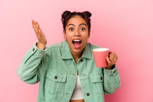 ピンクの背景にマグカップを持った若いラテン女性が、嬉しい驚きを受け取り、興奮して手を上げている。