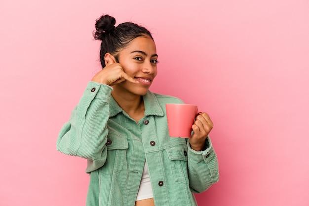 指で携帯電話の呼び出しジェスチャーを示すピンクの背景に分離されたマグカップを保持している若いラテン女性。