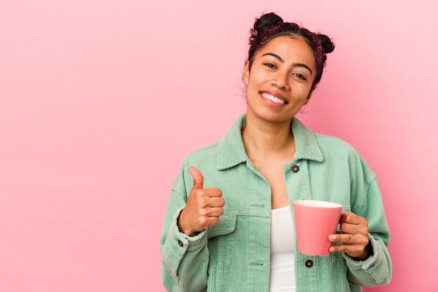 ピンクの背景に分離されたマグカップを持った若いラテン女性が笑顔で親指を上げる