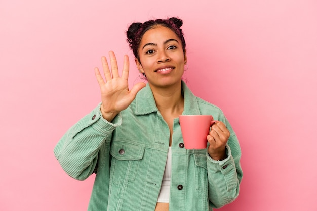 ピンクの背景にマグカップを持った若いラテン女性が指で5番を示す陽気な笑顔。