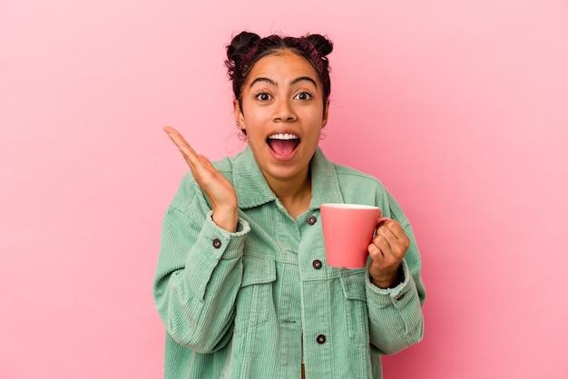 Молодая латинская женщина, держащая кружку на розовом фоне, удивлена и шокирована.