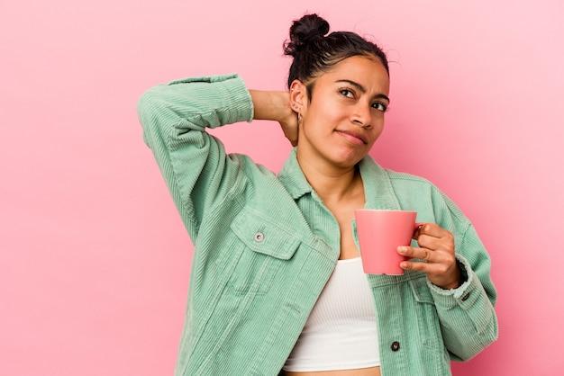 Молодая латинская женщина держит кружку, изолированную на розовом фоне, касаясь затылка, думая и делая выбор.
