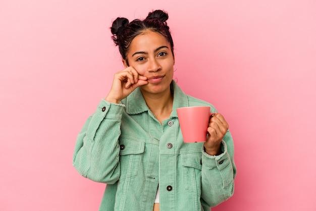 秘密を守る唇に指でピンクの背景に分離されたマグカップを保持している若いラテン女性。