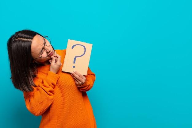 疑問符の看板を保持している若いラテン女性