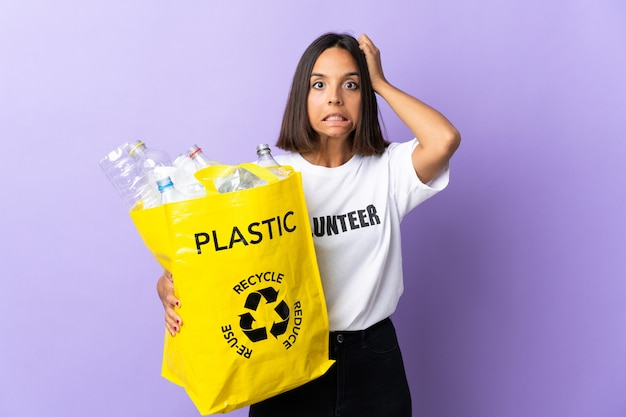 Молодая латинская женщина держит мешок для переработки, полный бумаги для переработки, изолированную на фиолетовом, делая нервный жест