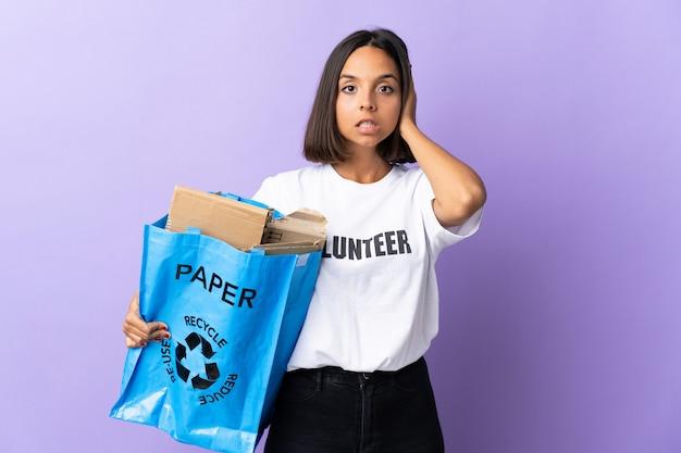 Молодая латинская женщина, держащая мешок рециркуляции, полный бумаги для переработки, изолированные на фиолетовые расстроенные и конические уши