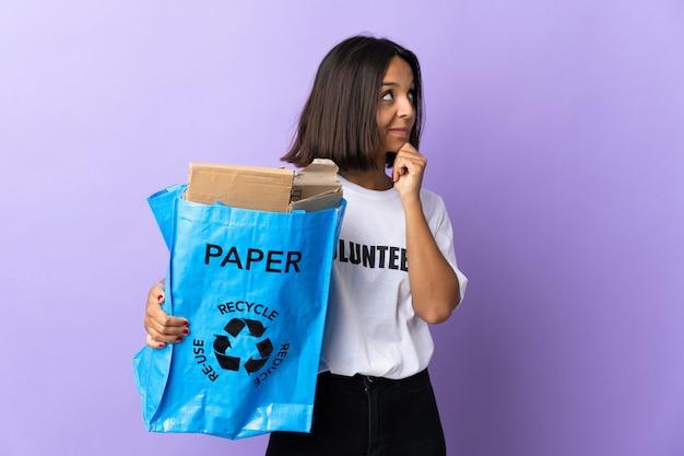 Молодая латинская женщина держа мешок рециркулировать полный бумаги для рециркуляции изолировала на пурпуре имея сомнения и думая