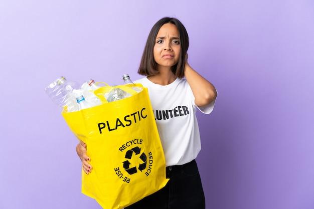 Молодая латинская женщина держа рециркулировать сумку полный бумаги для рециркуляции изолированная на пурпуре имея сомнения