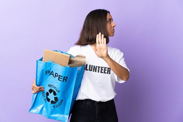 Молодая латинская женщина, держащая мешок для переработки, полный бумаги для переработки, изолирована на фиолетовом, делая жест стоп и разочарована