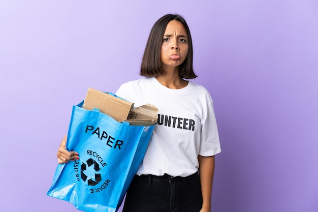 Молодая латинская женщина держит мешок для переработки, полный бумаги для переработки, изолированную на фиолетовом с грустным выражением лица