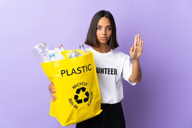 Молодая латинская женщина держит мешок для переработки, полный бумаги для переработки