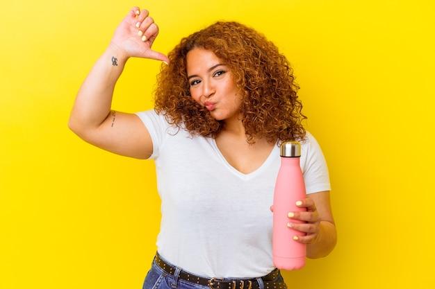 黄色の背景に魔法瓶を持った若いラテン女性は、誇りと自信を持っていると感じています。