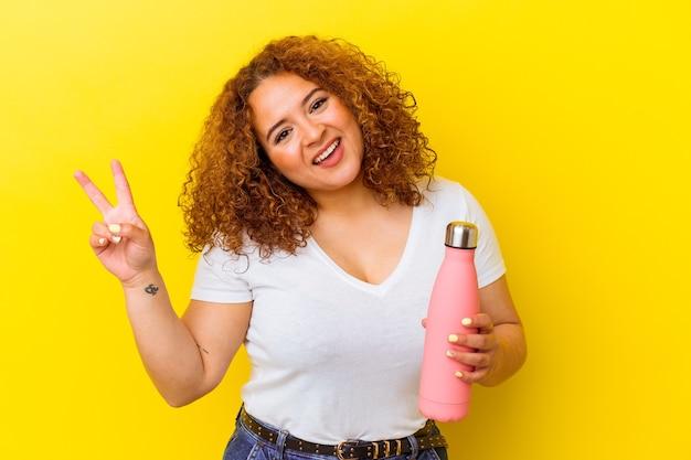 黄色の背景に魔法瓶を持った若いラテン女性が、指で平和のシンボルを示す、うれしくて屈託のない
