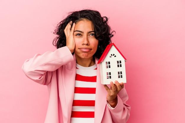 충격을 받고 분홍색 배경에 고립 된 장난감 집을 들고 젊은 라틴 여자, 그녀는 중요한 회의를 기억했습니다.