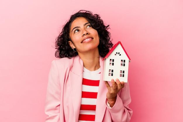 目標と目的を達成することを夢見てピンクの背景で隔離のおもちゃの家を保持している若いラテン女性