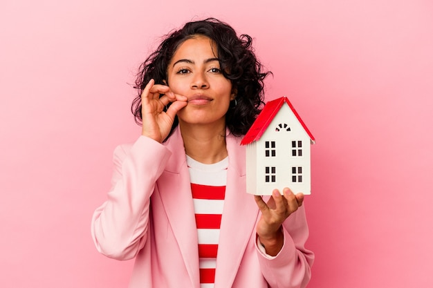 秘密を守る唇に指でピンクの背景に隔離されたおもちゃの家を保持している若いラテン女性。