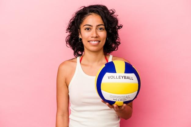 행복 하 고 웃 고 쾌활 한 분홍색 배경에 고립 된 배구를 들고 젊은 라틴 여자.