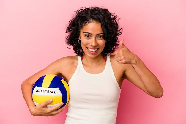 ピンクの背景で隔離のボレーボールを保持している若いラテン女性