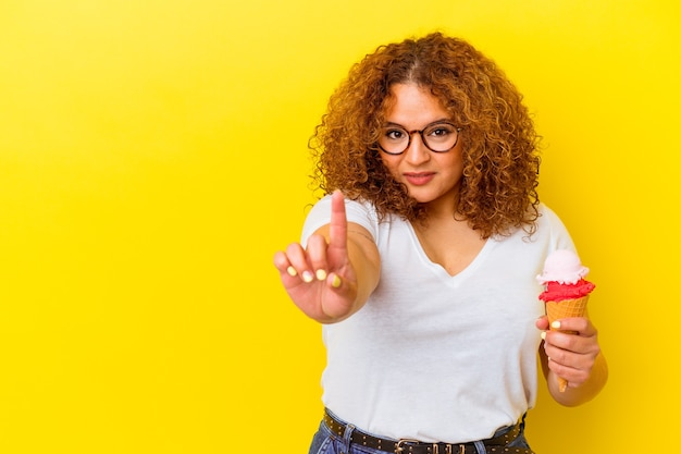 Молодая латинская женщина, держащая мороженое, изолирована на желтом фоне, показывая номер один пальцем.