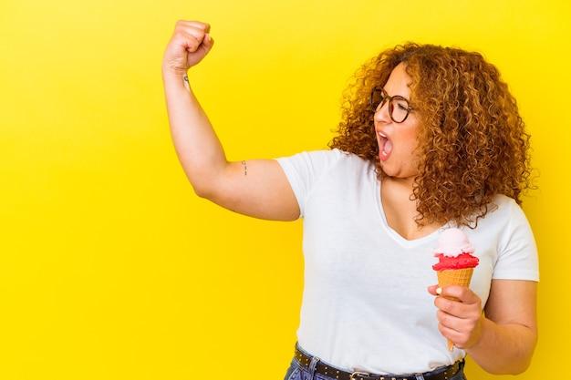승리 후 주먹을 올리는 노란색 벽에 고립 된 아이스크림을 들고 젊은 라틴 여자