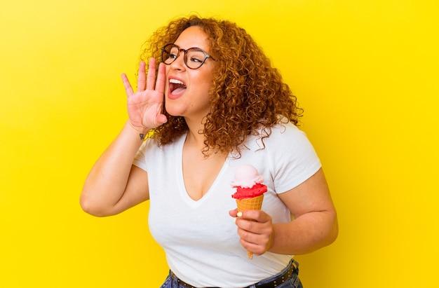 노란색 벽 소리에 고립 된 아이스크림을 들고 젊은 라틴 여자는 열린 입 근처에 손바닥을 들고