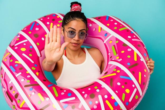 당신을 방지하는 정지 신호를 보여주는 뻗은 손으로 서 파란색 배경에 고립 된 풍선 도넛을 들고 젊은 라틴 여자.