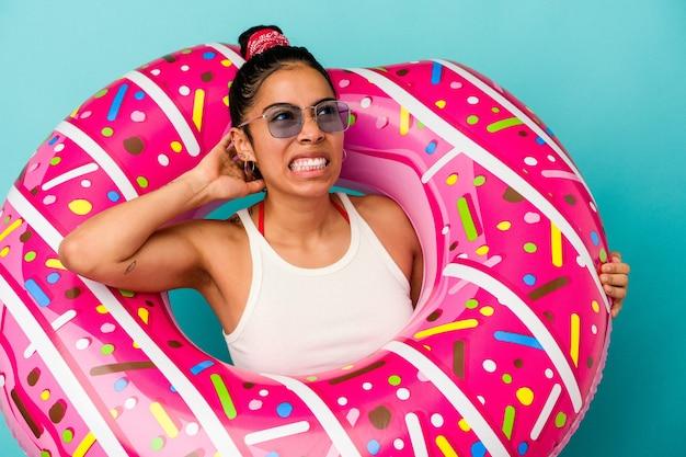 Молодая латинская женщина держит надувной пончик на синем фоне, касаясь затылка, думая и делая выбор.