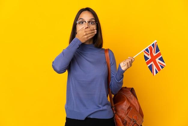 手で口を覆う黄色の背景に分離されたイギリスの旗を保持している若いラテン女性