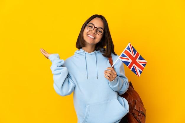 黄色の背景に分離されたイギリスの旗を持っている若いラテン女性は、来て招待するために手を横に伸ばします