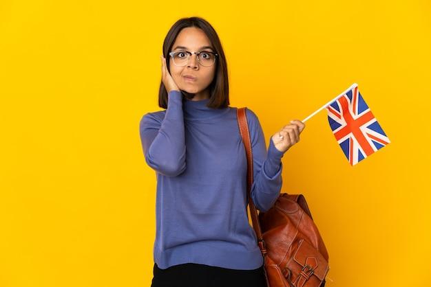 欲求不満と耳を覆っている黄色の背景に分離されたイギリスの旗を保持している若いラテン女性