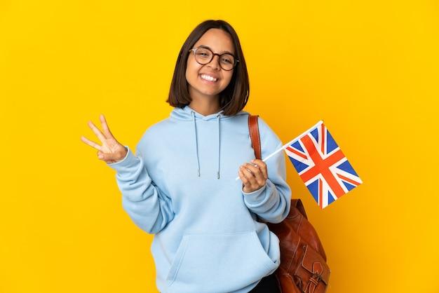 노란색 배경에 행복하고 손가락으로 세 세에 고립 된 영국 국기를 들고 젊은 라틴 여자