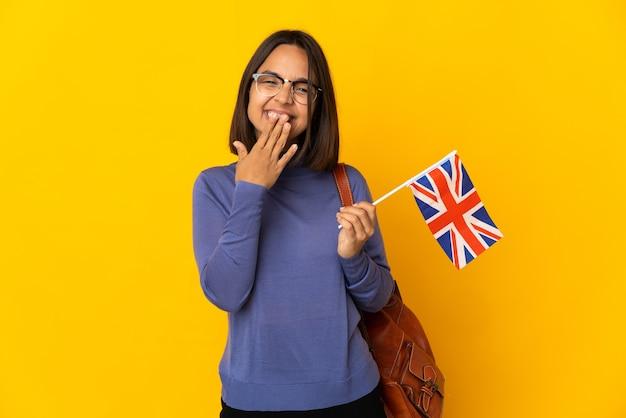 黄色の背景に分離されたイギリスの旗を保持している若いラテン女性幸せと笑顔の手で口を覆う