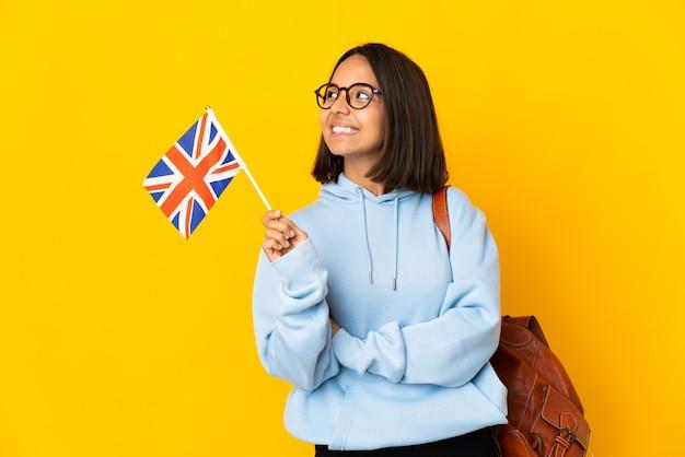 幸せと笑顔の黄色の背景に分離されたイギリスの旗を保持している若いラテン女性